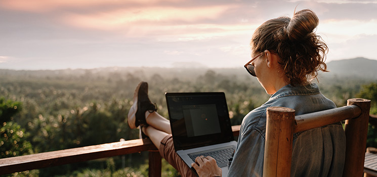 Young girl working on a laptop at sunset on the top of the mountain
