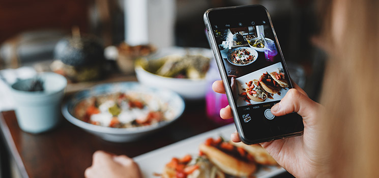 woman taking photo of a large spread of food